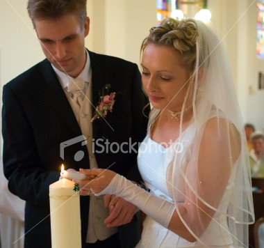 ist2_2326776-bride-and-groom-lighting-candle1